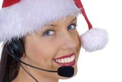 Zbliżenie atrakcyjna żeńska centrum telefoniczne telefonistka jest ubranym Bożenarodzeniowego Santa kapelusz, odizolowywający na  Zdjęcia Royalty Free