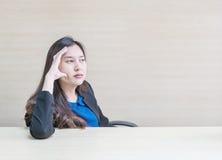 Zbliżenie azjatykcia kobieta pracuje z główkowanie twarzy emocją na zamazanej drewnianej biurka i drewna ścianie textured tło w p Obrazy Royalty Free
