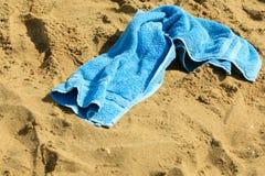Zbliżenie błękitny ręcznik na piaskowatej plaży relaksuje Obrazy Royalty Free