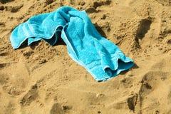 Zbliżenie błękitny ręcznik na piaskowatej plaży relaksuje Fotografia Stock