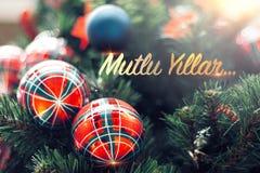 Zbliżenie błyszczący czerwony bauble obwieszenie od dekorującej choinki Mutlu Yillar znaczy Szczęśliwego nowego roku zdjęcia stock