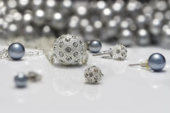 Zbliżenie biżuterii sety nabijający ćwiekami perła kolczyki, breloczki na akrylowej desce srebra i czerni i Fotografia Stock