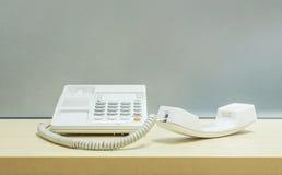Zbliżenie biały telefon, biurowy telefon na zamazanym drewnianym biurku i frosted szklana ściana, textured tło w pracy biurze Zdjęcia Stock