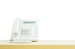 Zbliżenie biały telefon, biurowy telefon na zamazanym drewnianym biurku w pokoju konferencyjnym pod okno światłem na białym tle Obrazy Stock