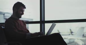 Zbliżenie biznesmen czekać na jego abordaż przepustkę w lotnisku, on pracuje na jego mówieniu na jego telefonie i laptopie zbiory wideo