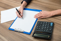 Zbliżenie biznesowej kobiety ręki podczas gdy pisać puszkowi niektóre istotnej ilościowej informaci Fotografia Royalty Free
