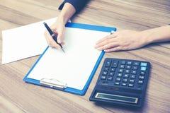 Zbliżenie biznesowej kobiety ręki podczas gdy pisać puszkowi niektóre istotnej ilościowej informaci Zdjęcia Royalty Free