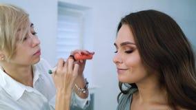 Zbliżenie blondynki makeup artysta robi fachowemu makeup dla brunetki ślicznej kobiety przy piękno salonem zbiory