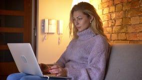 Zbliżenie bocznego widoku krótkopęd dorosła caucasian atrakcyjna kobieta pisać na maszynie na laptopie i ono uśmiecha się szczęśl zbiory wideo