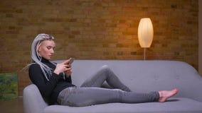 Zbliżenie bocznego widoku krótkopęd młoda atrakcyjna caucasian modniś kobieta używa telefonu siedzieć laidback na leżance zdjęcie wideo