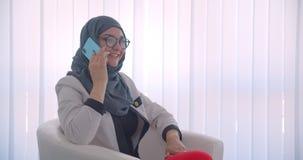 Zbliżenie bocznego widoku portret młoda muzułmańska kobiety lekarka w hijab i biel pokrywamy mieć rozmowy telefoniczej obsiadanie zbiory wideo