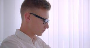 Zbliżenie bocznego widoku portret młody przystojny caucasian biznesmen obraca kamera indoors w białym pokoju w szkłach zdjęcie wideo
