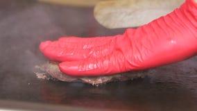 Zbliżenie Bocznego widoku ręki w Czerwonych rękawiczkach Obracają Cutlet zdjęcie wideo