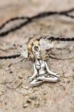 Zbliżenie bransoletka z joga dziewczyną w lotosowej pozyci obrazy royalty free