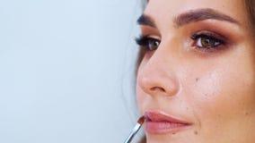 Zbliżenie brunetki kobiety kładzenia wargi młoda śliczna glosa z makeup muśnięciem zdjęcie wideo
