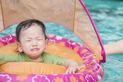 Zbliżenie chłopiec siedzi w łodzi dla dzieci w pływackiego basenu tle w strach emoci zdjęcie stock