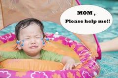 Zbliżenie chłopiec siedzi w łodzi dla dzieci w pływackiego basenu tle w strach emoci i potrzebuje pomoc jego mamą fotografia stock