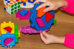 Zbliżenie child& x27; s ręka bierze jaskrawe mozaik części uczyć się barwi w domu Obrazy Royalty Free