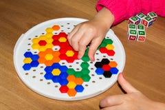 Zbliżenie child& x27; s ręki bierze jaskrawe mozaik części uczyć się barwi w domu Zdjęcia Royalty Free