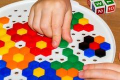 Zbliżenie child& x27; s ręki bierze jaskrawe mozaik części uczyć się barwi w domu Fotografia Stock
