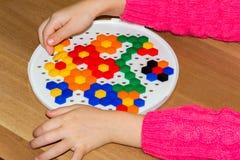 Zbliżenie child& x27; s ręki bierze jaskrawe mozaik części uczyć się barwi w domu Obraz Royalty Free