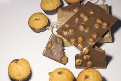Zbliżenie cukierki, czekolada z dokrętkami i słodka bułeczka na białym tle, zdjęcie stock