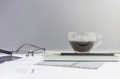 Zbliżenie czarna kawa w filiżance kawy na nutowej książce i ołówku z praca papierem na zamazanym drewnianym biurku i szklanej ści zdjęcia stock