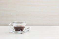 Zbliżenie czarna kawa w przejrzystej filiżance kawy na zamazanym drewnianym biurku i ścianie textured tło w pokoju konferencyjnym obraz royalty free