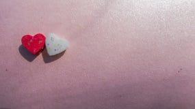Zbliżenie czerwoni i biali serca kształtuje na różowym tle Zdjęcie Royalty Free