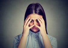 Zbliżenie deprymował smutnej kobiety patrzeje w dół opierający głowę na ręce obrazy stock