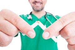 Zbliżenie doktorski ręki łamania papieros obrazy stock