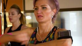 Zbliżenie dorosła kobieta używa sprawność fizyczna tropiciela przyrząd out w gym i pracujący zbiory