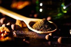 Zbliżenie drewniana nieociosana łyżka wypełniająca up z świeżym ziołowej herbaty proszkiem, innymi herbatami i pikantność w tle,  obraz stock