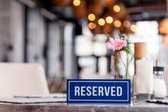 Zbliżenie drewniany błękitny biały prostokątny talerz z słowem Rezerwował pozycję na szarym rocznika stole w restauracyjnym blisk obrazy stock
