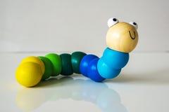 Zbliżenie drewno, kolorowy, dzieciaki, zabawkarska gąsienica na białych półdupkach Zdjęcie Stock