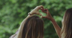 Zbliżenie duży serce od ręk, uśmiecha się piękne dziewczyny zbiory wideo