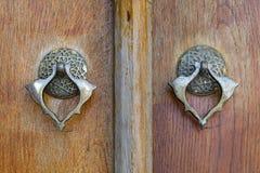 Zbliżenie dwa antyka miedzianego ozdobnego drzwiowego knockers nad starzejącym się drewnianym ozdobnym drzwi Zdjęcie Stock