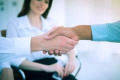 zbliżenie Dwa biznesmenów wielokulturowy handshaking nad biurkiem zdjęcia stock