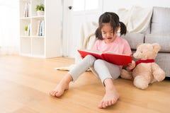 Zbliżenie dzieci czyta opowieść jej miś pluszowy Obrazy Royalty Free