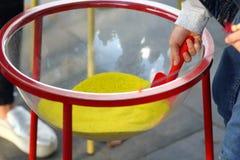 Zbliżenie dziecka ` s ręka z łopatą bierze żółtego kolorowego piasek z plastikowego pucharu obraz royalty free