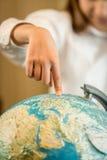 Zbliżenie dziewczyny mienia palec wskazujący na Ziemskiej kuli ziemskiej Zdjęcie Stock