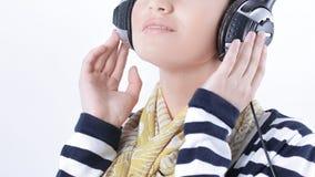 zbliżenie elegancka dziewczyna słucha muzyka z hełmofonami obraz royalty free