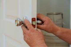 Zbliżenie fachowy locksmith instaluje nowego deadbolt kędziorek lub naprawia obraz royalty free