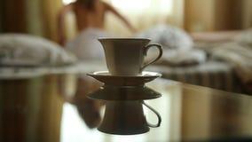 Zbliżenie filiżanka gorąca herbata lub kawa, młoda seksowna kobieta rozbiera się i iść łóżko przy nocą Zamazana ostrość zbiory wideo