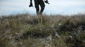 Zbliżenie fotografa stopa czyj sylwetka iść poza horyzont w defocus Fotograf chodzi przez a zdjęcie wideo