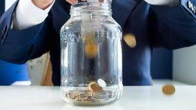 Zbliżenie fotografia monety spada dla businessmans ręk w szklanym słoju Pojęcie bogactwo i bogactwo zdjęcia royalty free