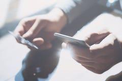 Zbliżenie fotografii biznesmena mienia ręki kredytowa karta i używać smartphone Online zapłata klingerytu karta horyzontalny Mock obrazy royalty free