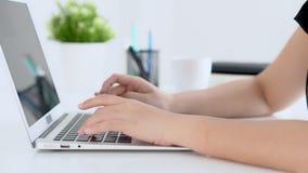 Zbliżenie freelance kobiety uśmiechnięty działanie i pisać na maszynie na laptopie przy biurka biurem z profesjonalistą zbiory