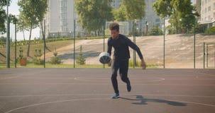 Zbliżenie frontowy portret młodego atrakcyjnego amerykanin afrykańskiego pochodzenia męski gracz koszykówki rzuca piłkę w obręcz  zbiory