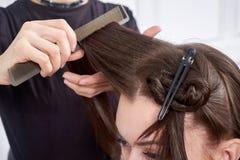 Zbliżenie fryzjer robi fryzurze dla młodej kobiety w piękno salonie obraz royalty free